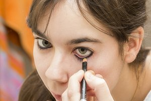 woman applying makeup eyes