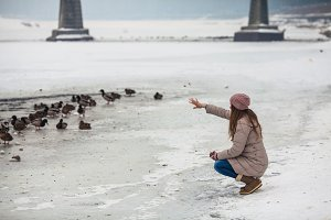 Girl feeding ducks in winter