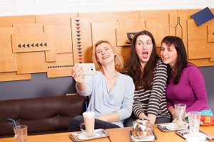 Funny selfie friends in a cafe