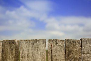 Blue cloudy sky behind a wooden fence. Texture background