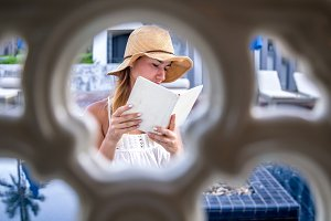 girl in a hat reading a book on holiday