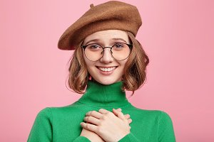 Portrait of smiling positive woman keeps hand on chest, expresses her sympathy. Kind hearted friendly young female shows kindness, wears beret and green turtleneck sweater, has joyful expression.