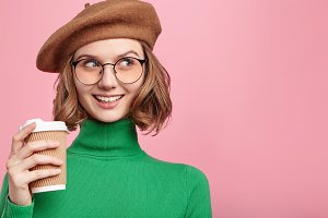 Pensive dreamy lovely woman wears retro clothes, waits for someone, holds takeaway coffee, poses against pink background with copy space for your advertisment. People, liesure, beauty concept