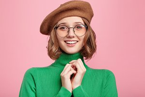 Positive adorable female model smiles happily, glad to recieve pleasant news from interlocutor, keeps hands together, wears old fashionable clothes. People, retro style and emotions concept.
