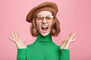 Dissatisfied old fashionable female wonk closes eyes and screams loudly, gestures, being very emotional after passing exam, isolated over pink background. Attractive woman in beret poses at studio