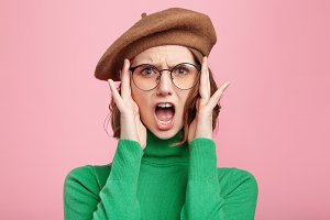 Portrait of indignant shocked pretty female wears beret, green turtleneck sweater and glasses, keeps mouth opened being surprised to hear bad comments of her work, feels disturbed and offended
