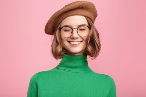 Horizontal portrait of dreamful positive female in retro outfit stands over pink background with closed eyes, imagines something pleasant, tries to relax. Positive human emotions and feelings concept