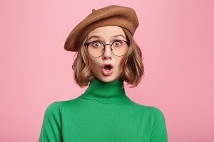 Horizontal shot of astonished beautiful female model wears green turtleneck sweater and glasses, looks with bugged eyes and widely opened mouth, surprised to observe terrified scene on street