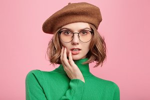 Pretty female students wears retro clothes listens attentively professor`s lecture, has serious expression, tries to understand everything. Cute woman in beret and turteneck sweater isolated on pink