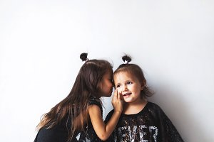 Two little girls in mother's dresses