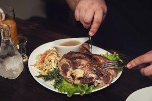 Man eats tasty dish of pork shank
