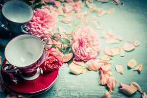 Tea cups and pink roses on turquoise