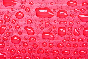 Abstract background of water droplets on red surface.