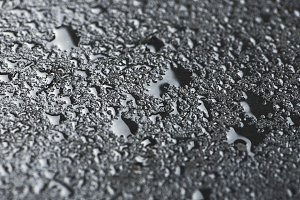 Abstract background of water drops on black slate surface.