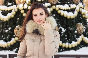 Young woman in winter park near christmas tree