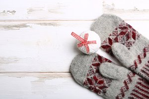Warm Christmas. Knitted mittens and a Christmas tree toy. New Year holiday background