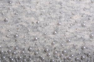 Knitted background. Light gray gentle wool background pattern. Background embroidered with beads