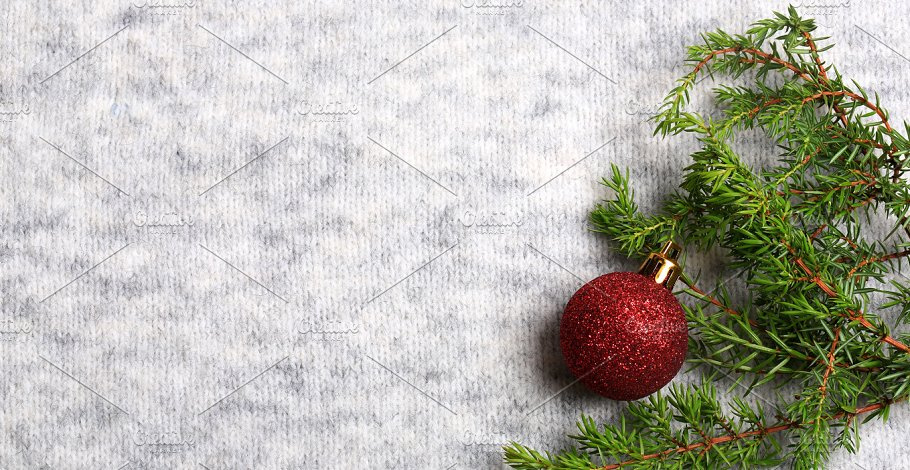 new year holiday background christmas tree toy and a spruce branch on a knitted gray background christmas composition