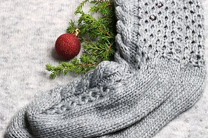 New Year holiday background. Knitted socks, Christmas tree toy and a spruce branch on a knitted gray background. Christmas composition