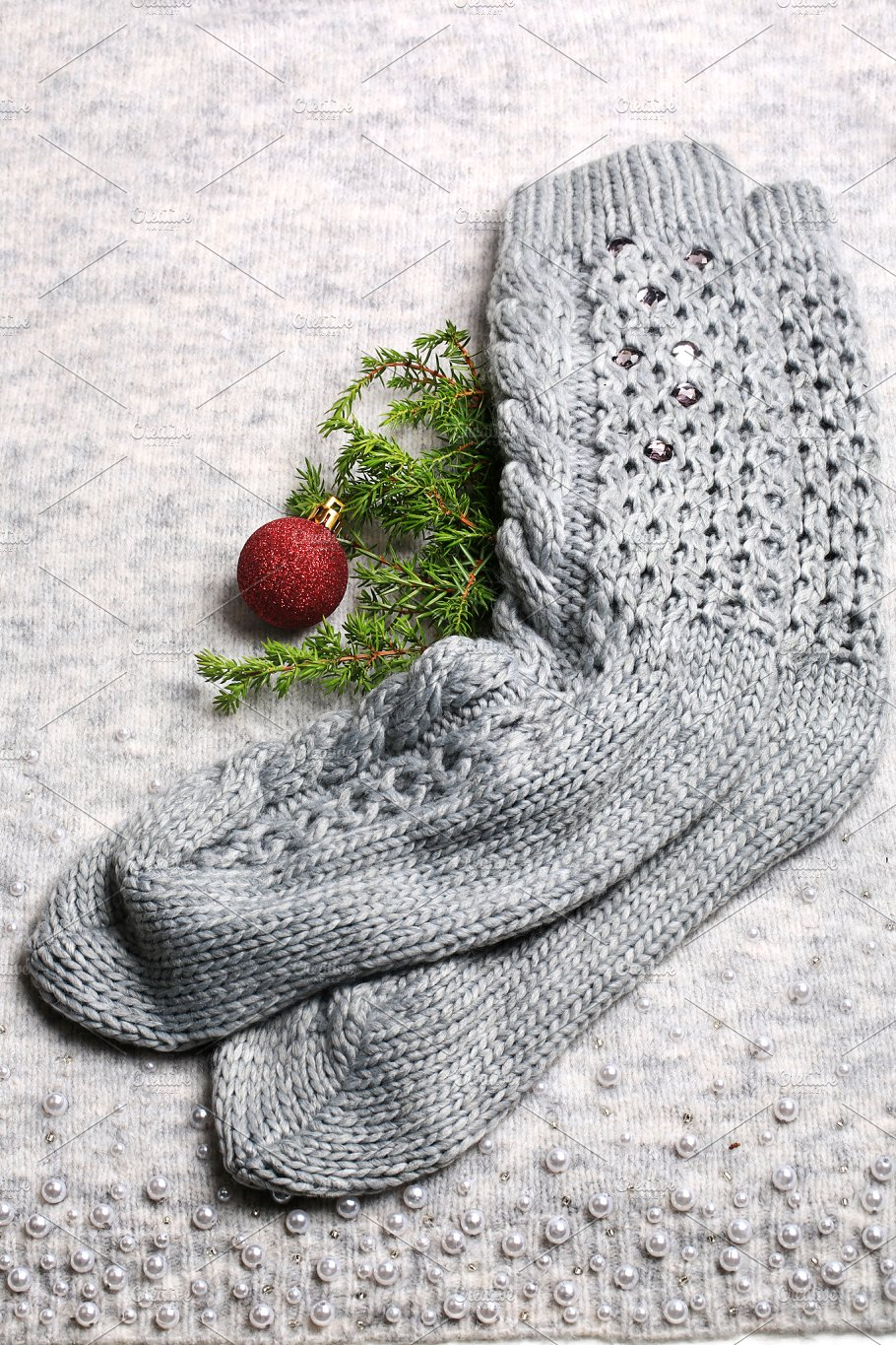 new year holiday background knitted socks christmas tree toy and a spruce branch on a knitted gray background christmas composition