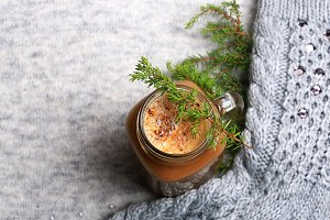 Christmas winter coffee with a spruce branch on a knitted gray background