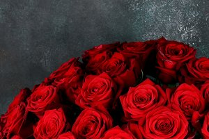 bouquet of red roses on a dark grunge background Flat lay, copyspace.