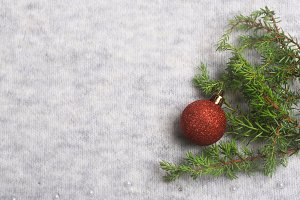 New Year holiday background. Christmas tree toy and a spruce branch on a knitted gray background. Christmas composition