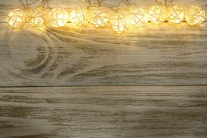 christmas garland lights on wooden rustic background with copy space for your text. Top view