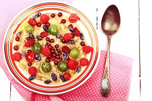 breakfast oatmeal with berries and honey on white wooden background flat style top view overhead summer menu