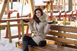 Young woman in winter park sitting on bench