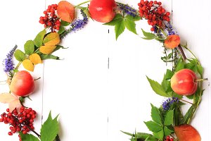 autumn wreath with flowers and berries on a white wooden background