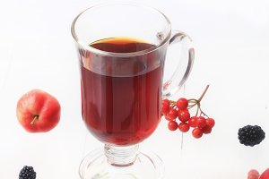autumn warming tea with berries on a white wooden background