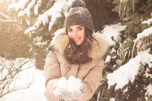 Young woman playing with snow