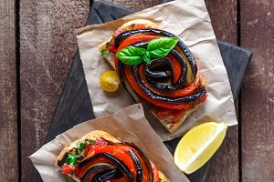 Two pieces of bruschetta with peppers, aubergine and basil.