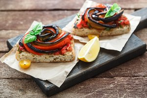 Tapas with baked aubergines and peppers on wooden board, rustic style