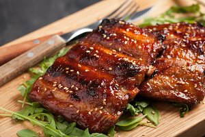 Closeup of pork ribs grilled with BBQ sauce and caramelized in honey on a bed of arugula. Tasty snack to beer on a wooden Board for filing on dark concrete background