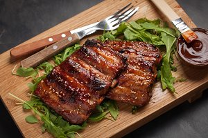 Closeup of pork ribs grilled with BBQ sauce and caramelized in honey on a bed of arugula. Tasty snack to beer on a wooden Board for filing on dark concrete background. Top view