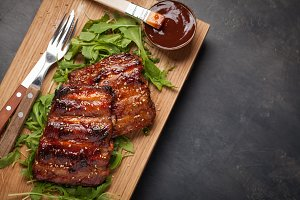 Closeup of pork ribs grilled with BBQ sauce and caramelized in honey on a bed of arugula. Tasty snack to beer on a wooden Board for filing on dark concrete background. Top view with copy space