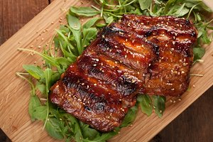 Closeup of pork ribs grilled with BBQ sauce and caramelized in honey on a bed of arugula. Tasty snack to beer on a wooden Board for submission on the old wooden background. Top view