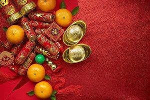 Chinese coins of luck or chinese knot and Chinese gold ingots and Traditional chinese knot  (Foreign text means blessing) and Red envelopes and decoration with Fresh oranges on Red background