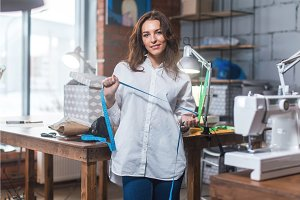 Portrait of pretty brunette fashion designer smiling, looking at camera standing in a sewing workshop against tools and equipment