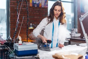 Young Caucasian female tailor ironing fabric with steam iron in a sewing workshop  modern loft interior