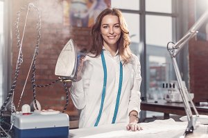 Portrait of attractive young Caucasian brunette dressmaker standing in white clothes holding steam iron in studio.