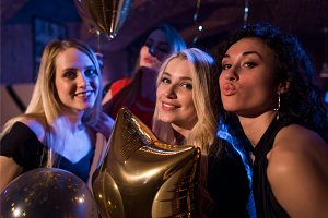 Pretty European girls smiling, blowing kisses having party at night club