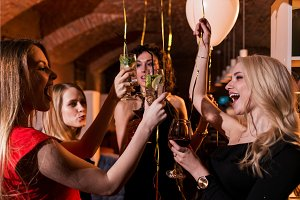 Happy attractive young women having birthday party laughing, dancing, singing, enjoying the night in stylish restaurant