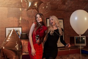 Two pretty women in cocktail dresses posing with balloons at birthday party in stylish cafe