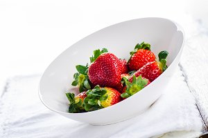 Fresh strawberries in bowl  on white