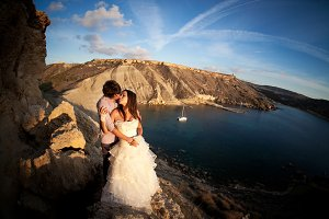 Groom kissing bride on the rocks