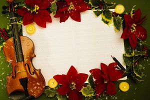 Violin and open music manuscript on the green background. Christmas concept