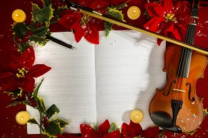 Violin and open music manuscript on the red background. Christmas concept